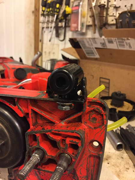 """Repaired front vibration isolator. Broken housing ring replaced with a section of 1/2"""" water pipe, bolted to the engine frame, filled with melted hot glue, hole drilled through center of plastic, rubber grommets on both ends."""