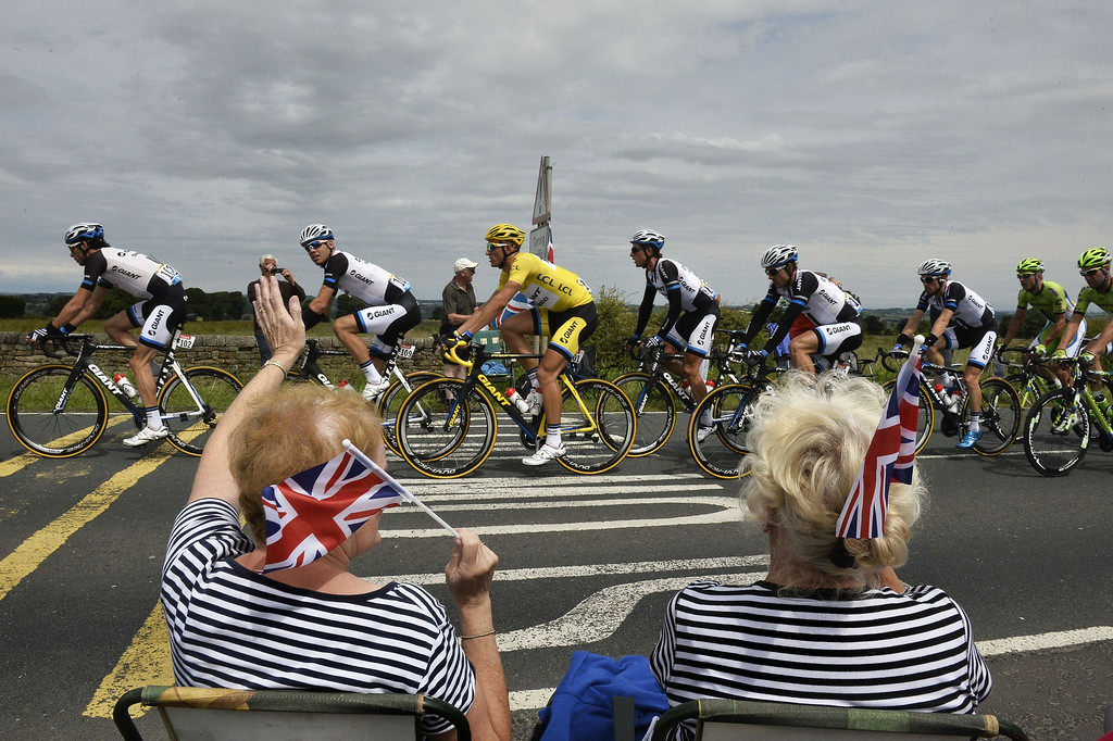 . Supporters wave along the road as Germany\'s Marcel Kittel (C), wearing the overall leader\'s yellow jersey, rides past during the 201 km second stage of the 101th edition of the Tour de France cycling race on July 6, 2014 between York and Sheffield, northern England.  AFP PHOTO / JEFF PACHOUDJEFF PACHOUD/AFP/Getty Images