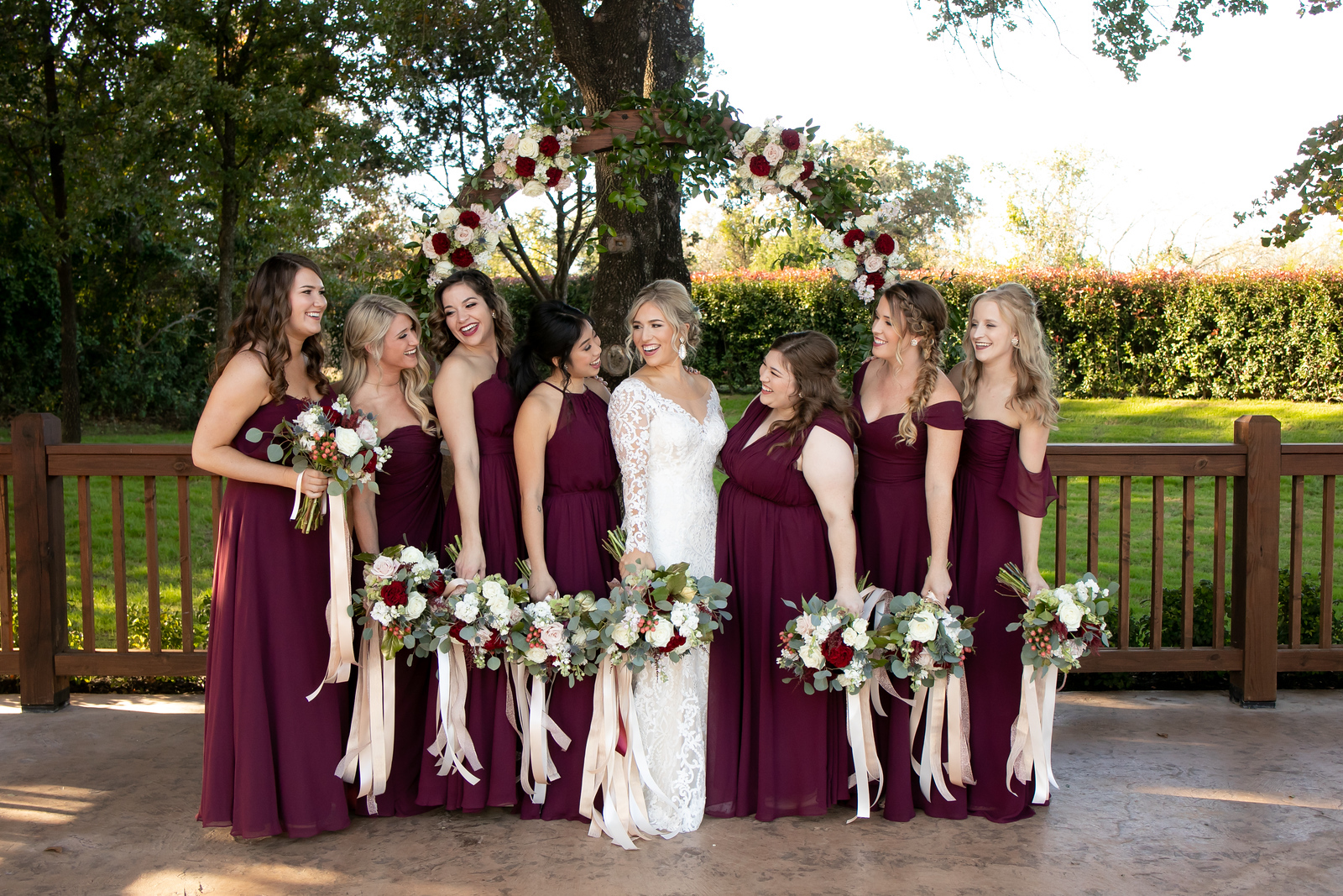 a bride posing for a photo with her seven bridesmaids wearing burgundy dresses all looking at her
