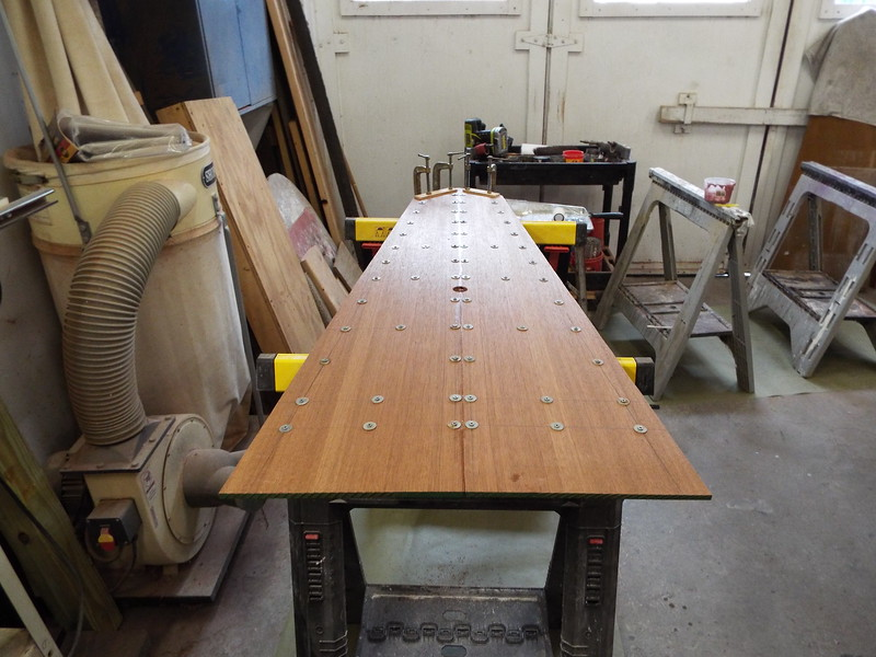 Mahogany skin applied held in place with temporary fasteners until the epoxy dries.