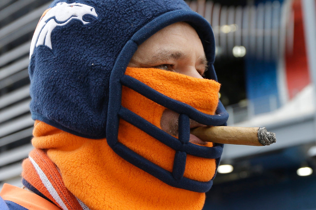 . Denver Broncos fan Steve Richards of Minneapolis smokes a cigar before the NFL Super Bowl XLVIII football game Sunday, Feb. 2, 2014, in East Rutherford, N.J. (AP Photo/Ben Margot)