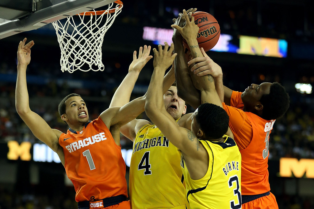 . ATLANTA, GA - APRIL 06:  Michael Carter-Williams (L) #1 and Jerami Grant #3 (R) of the Syracuse Orange fight for a rebound in the second half against Mitch McGary #4 and Trey Burke #3 of the Michigan Wolverines during the 2013 NCAA Men\'s Final Four Semifinal at the Georgia Dome on April 6, 2013 in Atlanta, Georgia.  (Photo by Streeter Lecka/Getty Images)