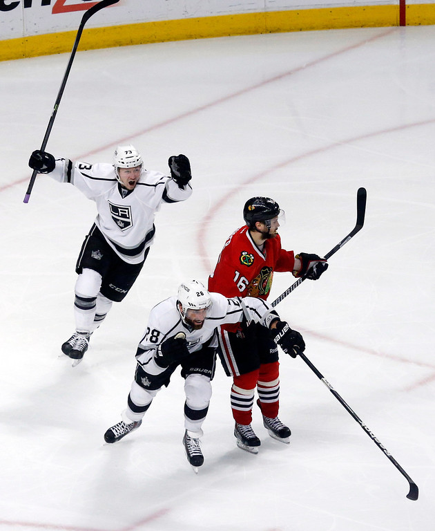 . Los Angeles Kings center Tyler Toffoli, left, celebrates the game winning goal with center Jarret Stoll (28) as they pass Chicago Blackhawks center Marcus Kruger (16) during the overtime period in Game 7 of the Western Conference finals in the NHL hockey Stanley Cup playoffs Sunday, June 1, 2014, in Chicago. The Kings won 5-4 in the overtime. (AP Photo/Charles Rex Arbogast)