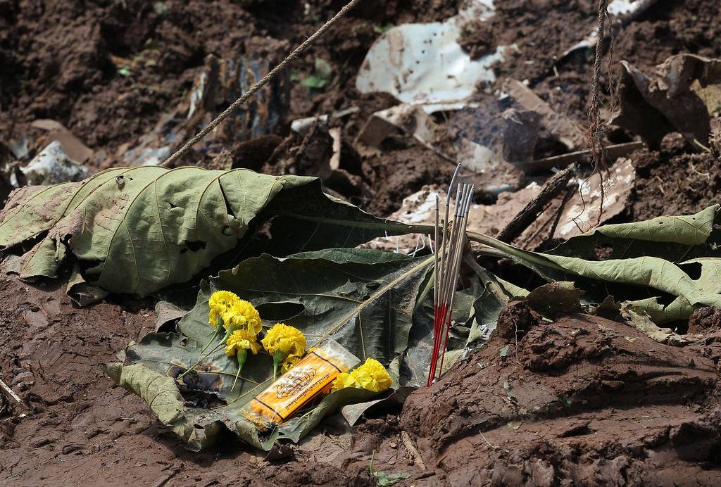 . Flowers and incense sticks are offered beside the wreckage of an ill-fated Lao Airlines plane that chased on the riverbank and sank in the Mekong River in Pakse in Laos Thursday, Oct. 17, 2013.  (AP Photo/Sakchai Lalit)