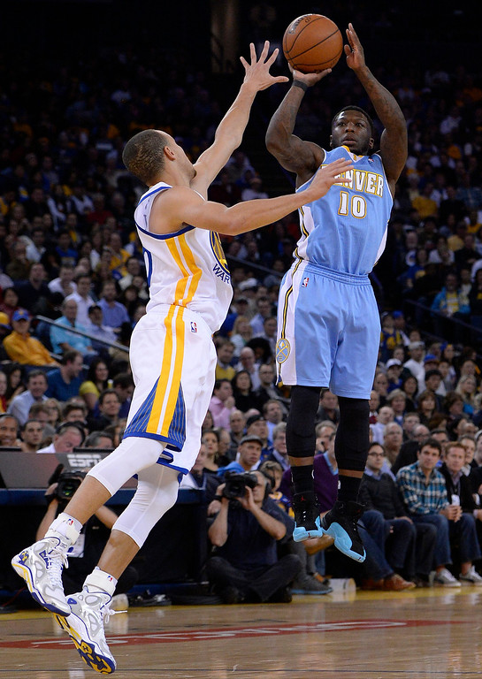 . Denver Nuggets point guard Nate Robinson (R) shoots over Golden State Warriors point guard Stephen Curry (L) during the first half of their NBA game at Oracle Arena.  EPA/JOHN G. MABANGLO CORBIS OUT
