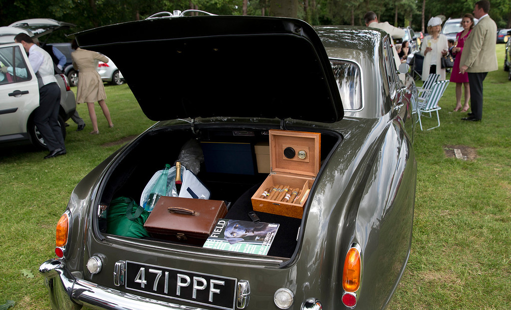 . A box of cigars with bottles of champagne are seen in the boot of a Rolls Royce car in the car park on the second day of the Royal Ascot horse racing meeting at Ascot, England,  Wednesday, June, 18, 2014.  (AP Photo/Alastair Grant)