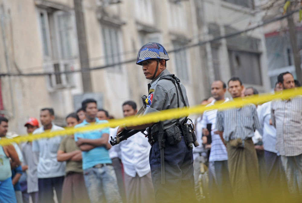 . Policemen stand guard in front of the Islamic school after a fire broke out at the school in downtown Yangon early April 2, 1013.  Thirteen people, including children, were killed after a fire broke out in a Muslim school in Yangon due to a suspected electrical fault, police in Myanmar\'s main city said.    AFP PHOTO / Soe Than WIN