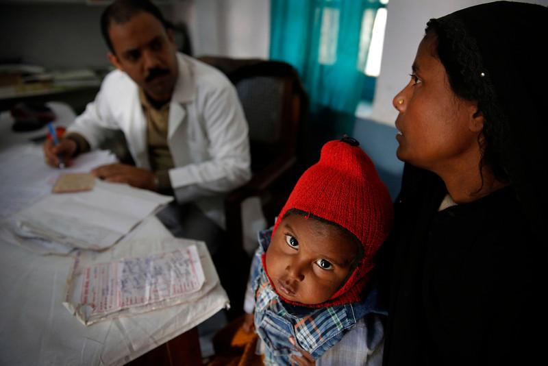 . In this Saturday, Feb. 1, 2014 photo, a doctor attends to Anwar, 4, infected with tuberculosis at the Kashi Vidyapith block hospital in Kotawa near Varanasi, India. (AP Photo/Rajesh Kumar Singh)
