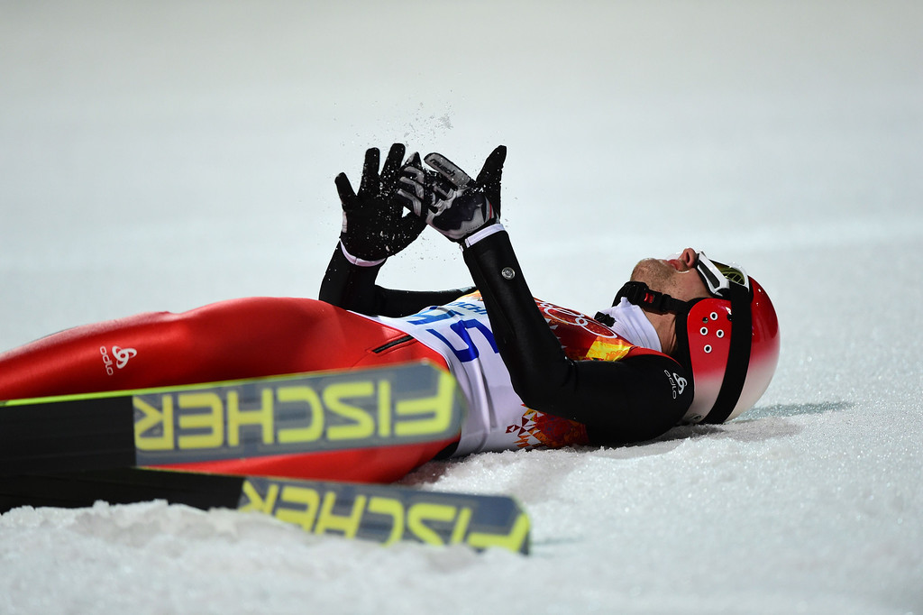 . Switzerland\'s Simon Ammann lies on the snow after competing in the Men\'s Ski Jumping Normal Hill Individual Final Round at the RusSki Gorki Jumping Center during the Sochi Winter Olympics on February 9, 2014 in Rosa Khutor. JOHN MACDOUGALL/AFP/Getty Images