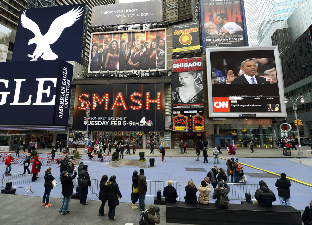 . Tourist watch on a Jumbotron in Times Square  in New York as US President Barack Obama (R) takes the oath of office during the 57th Presidential Inauguration ceremonial swearing-in at the US Capitol on January 21, 2013 in Washington, DC.  TIMOTHY A. CLARY/AFP/Getty Images