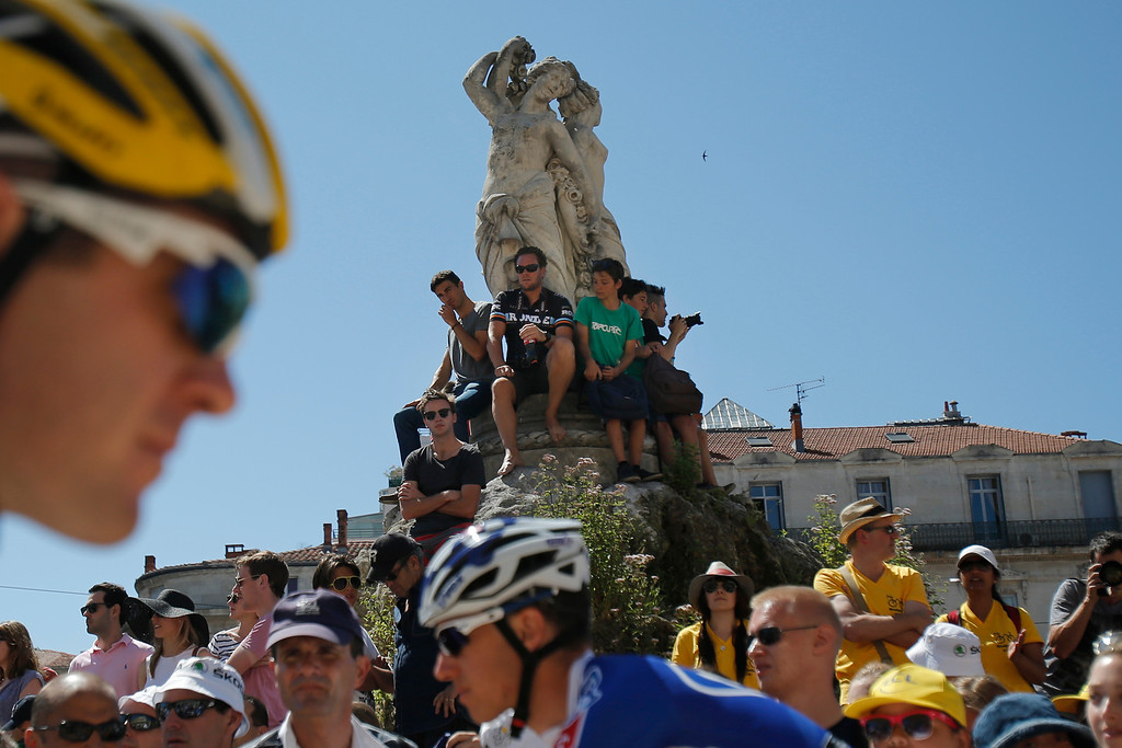 . Spectators watch from atop a statue as the pack gets ready to take the start of the seventh stage of the Tour de France cycling race over 205.5 kilometers (128.5 miles) with start in Montpellier and finish in Albi, southern France, Friday July 5, 2013. (AP Photo/Christophe Ena)