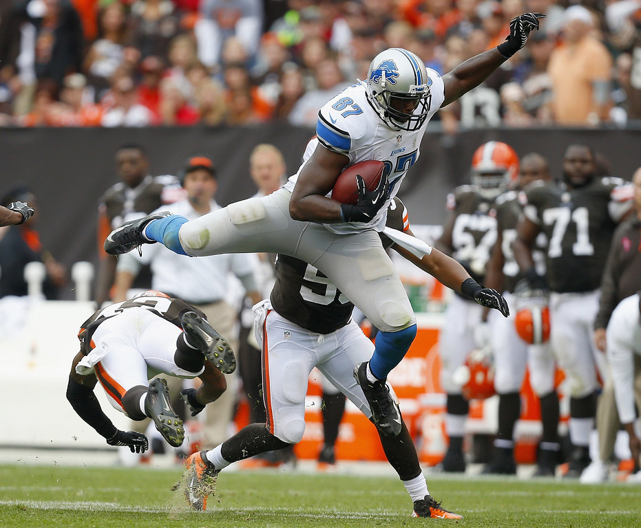 . Tight end Brandon Pettigrew #87 of the Detroit Lions dives jumps over defensive back T.J. Ward #43 of the Cleveland Browns at FirstEnergy Stadium on October 13, 2013 in Cleveland, Ohio.  (Photo by Matt Sullivan/Getty Images)