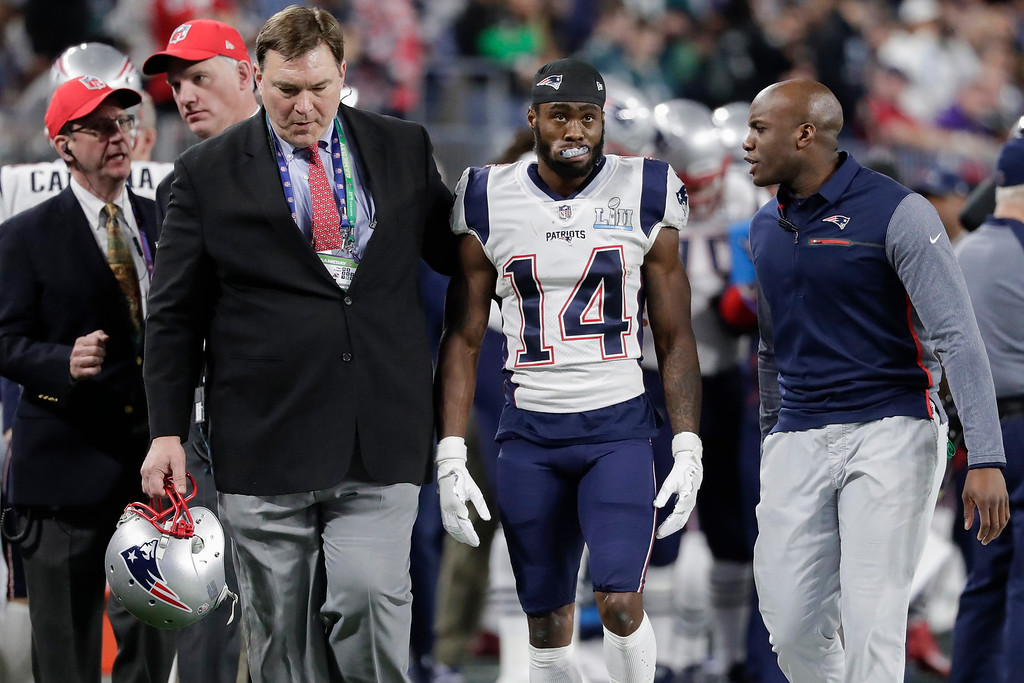 . New England Patriots trainers escort wide receiver Brandin Cooks (14) off the field, during the first half of the NFL Super Bowl 52 football game against the Philadelphia Eagles Sunday, Feb. 4, 2018, in Minneapolis. (AP Photo/Tony Gutierrez)
