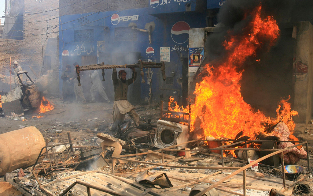 . An angry demonstrator burns furniture during a protest in the Badami Bagh area of Lahore March 9, 2013. An enraged mob torched dozens of houses located in a Christian-dominated neighbourhood of Lahore on Saturday, local media reported. REUTERS/Mani Rana