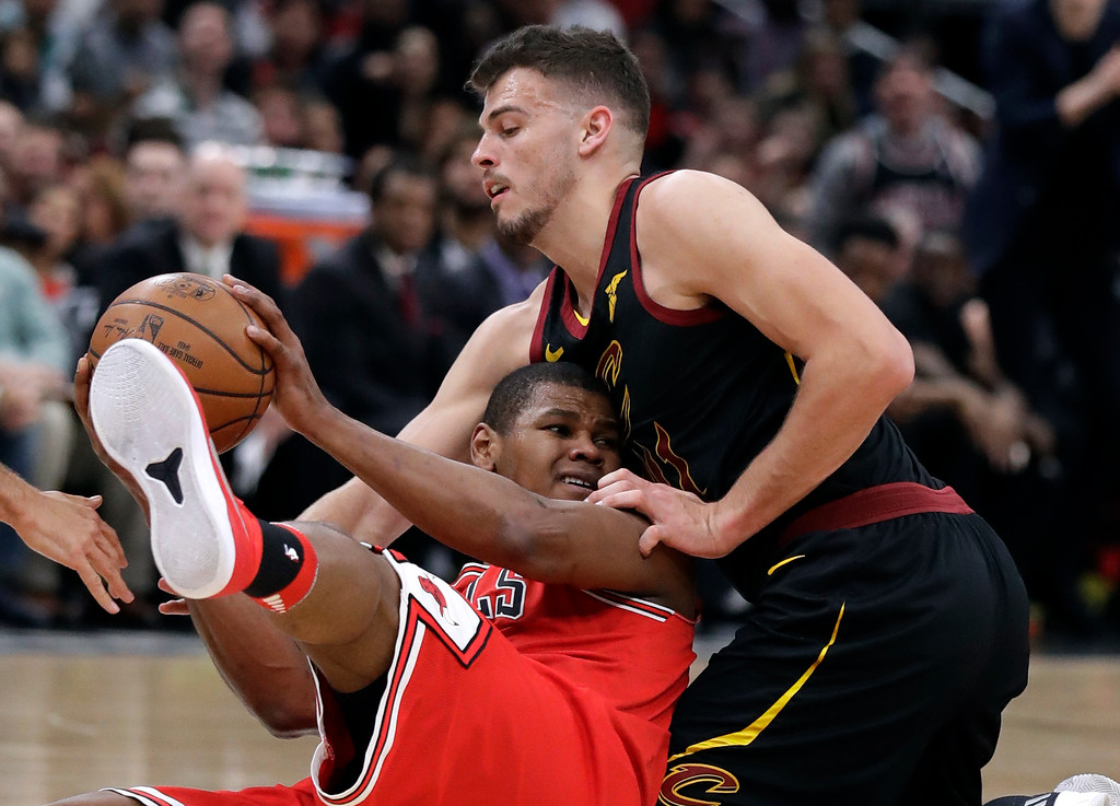 . Chicago Bulls center Cristiano Felicio, left, battles for a loose ball against Cleveland Cavaliers center Ante Zizic during the first half of an NBA basketball game Saturday, March 17, 2018, in Chicago. (AP Photo/Nam Y. Huh)