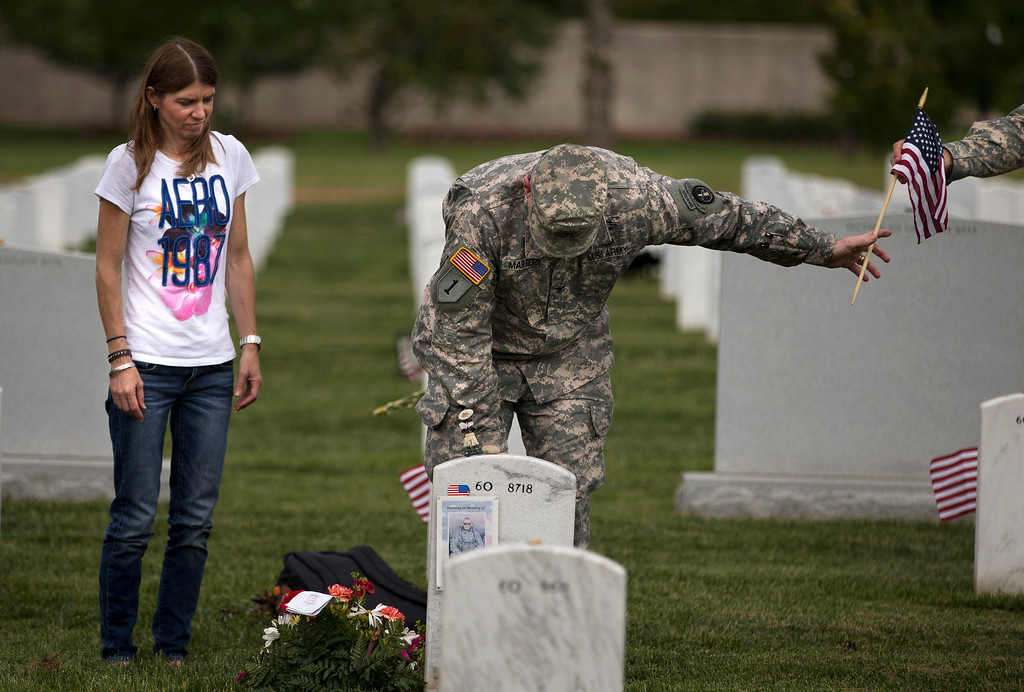 """. Jennifer Henderson, of Winston-Salem, N.C., watches as Col. Jim Market, of the 3rd U.S. Infantry Regiment, also known as The Old Guard, places a flag at the grave site of her husband Sgt. 1st Class Christopher Henderson, who was killed in Afghanistan on June 17, 2007, at Arlington National Cemetery as part of the annual \""""Flags-In\"""" ceremony in preparation for Memorial Day on Thursday, May 23, 2013, in Arlington, Va. (AP Photo/Evan Vucci)"""