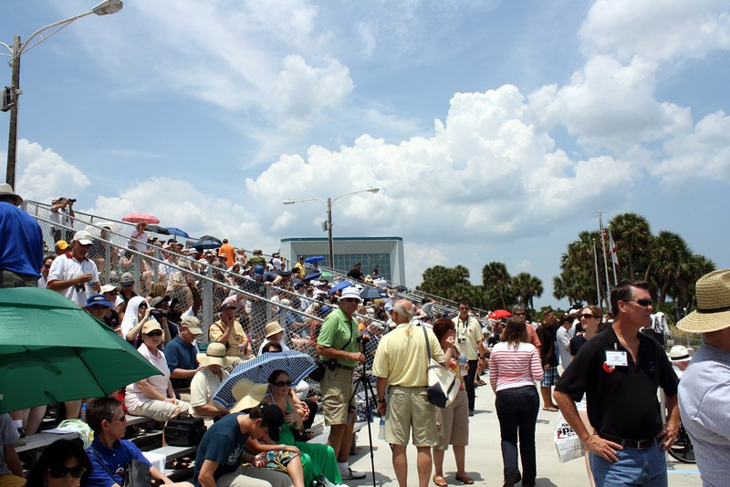 The VIP bleachers at the Banana Creek viewing area, with the Apollo / Saturn V Center in the background.  The umbrellas are for shade, not rain.