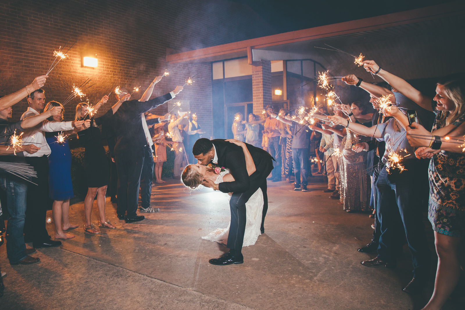a groom dipping his newlywed wife while their wedding guest stand around them with sparklers during their grand exit