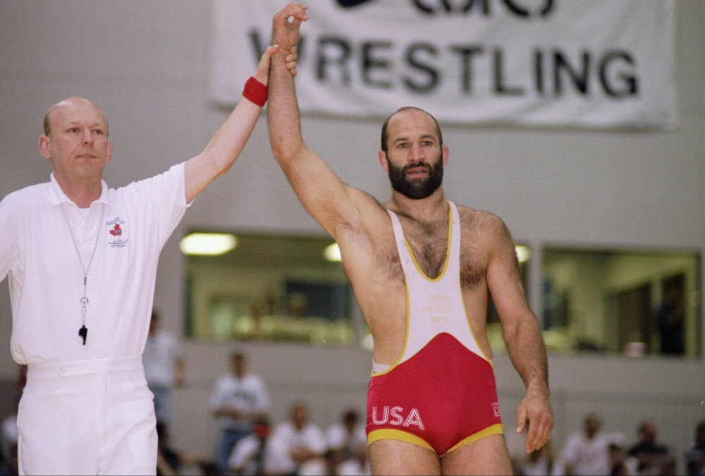 Description of . 6 May 1995: Dave Schultz (right) is declared the winner of a match during the United States National Wrestling competition in Las Vegas, Nevada. Schultz's won a gold medal at the 1984 Los Angeles Olympic Games. While training for the 1996 Atlanta Olympics, he was shot to death by millionaire John DuPont, who had recruited Schultz for a wrestling program he created.