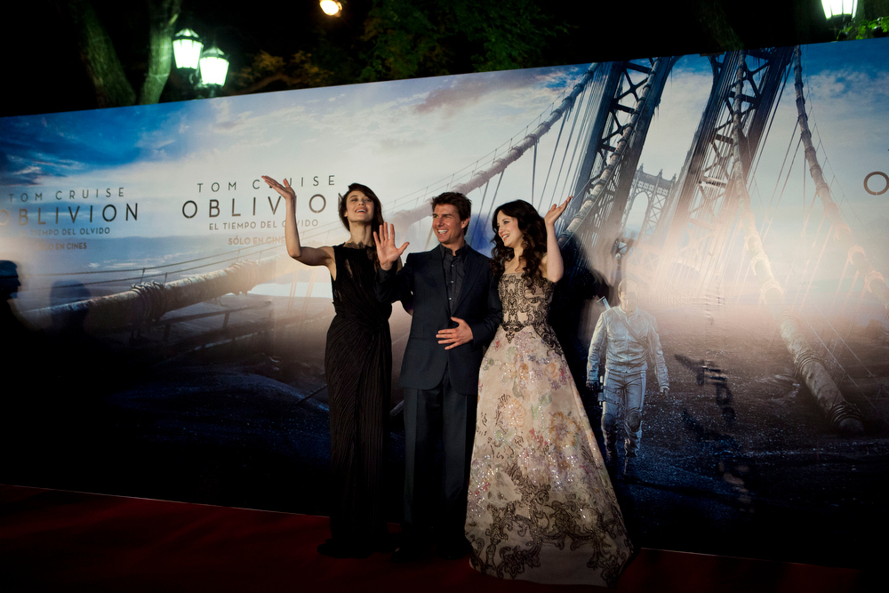 ". U.S. actor Tom Cruise, center, actress Olga Kurylenko, left, and Andrea Riseborough wave to media during a presentation to promote the film ""Oblivion\"" in Buenos Aires, Argentina,  Tuesday, March 26, 2013. (AP Photo/Natacha Pisarenko)"