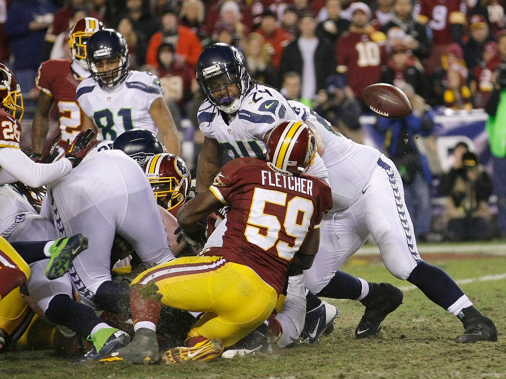Description of . Seattle Seahawks running back Marshawn Lynch (24) looks back as he fumbles the ball when hit by Washington Redskins inside linebacker London Fletcher (59) in the second half during their NFL NFC wildcard playoff game in Landover, Maryland, January 6, 2013. REUTERS/Laurence Kesterson