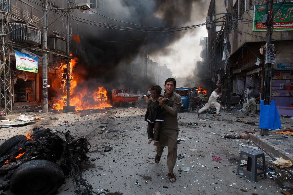 . A Pakistani man carrying a child rushes away from the site of a blast shortly after a car exploded in Peshawar, Pakistan, Sunday, Sept. 29, 2013. A car bomb exploded on a crowded street in northwestern Pakistan, killing scores of people in the third blast to hit the troubled city of Peshawar in a week. (AP Photo/Mohammad Sajjad)