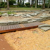 timber bridge and naturalistic sandpit with boulder edging