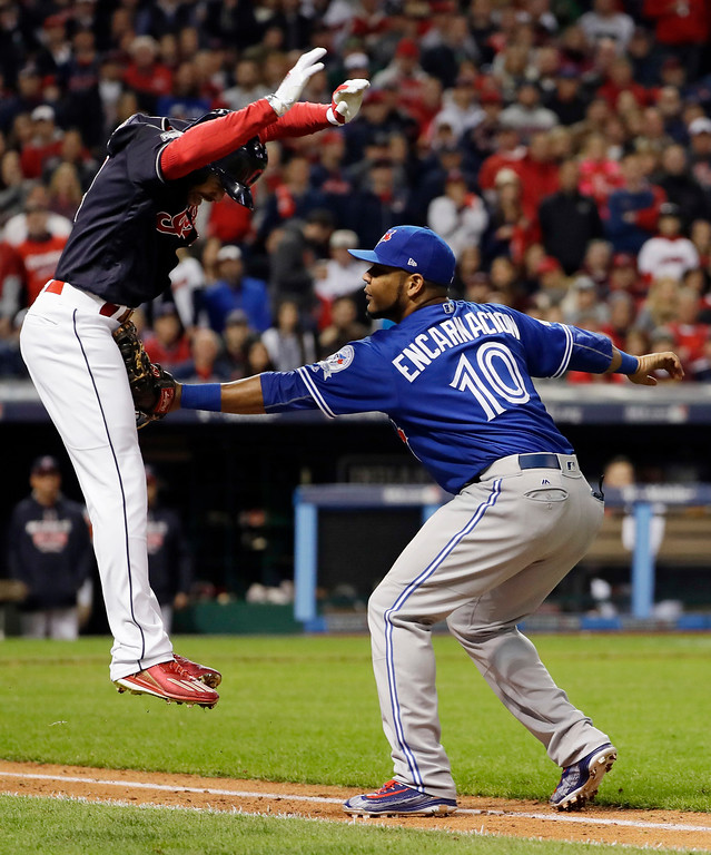 . Toronto Blue Jays first baseman Edwin Encarnacion, right, tags out Cleveland Indians\' Coco Crisp during the seventh inning in Game 1 of baseball\'s American League Championship Series in Cleveland, Friday, Oct. 14, 2016. (AP Photo/Matt Slocum)