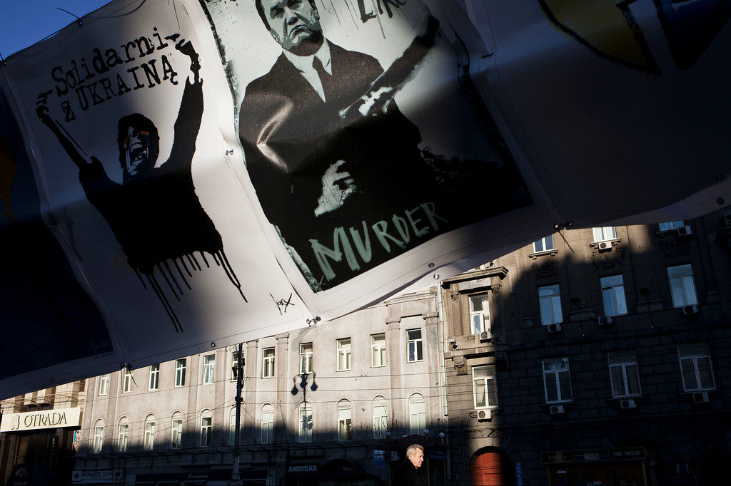 . A man is lit by the morning sun as he walks underneath a poster depicting Ukrainian President Victor Yanukovych near Kiev\'s Independence Square, in Ukraine, Wednesday, March 12, 2014. (AP Photo/David Azia)