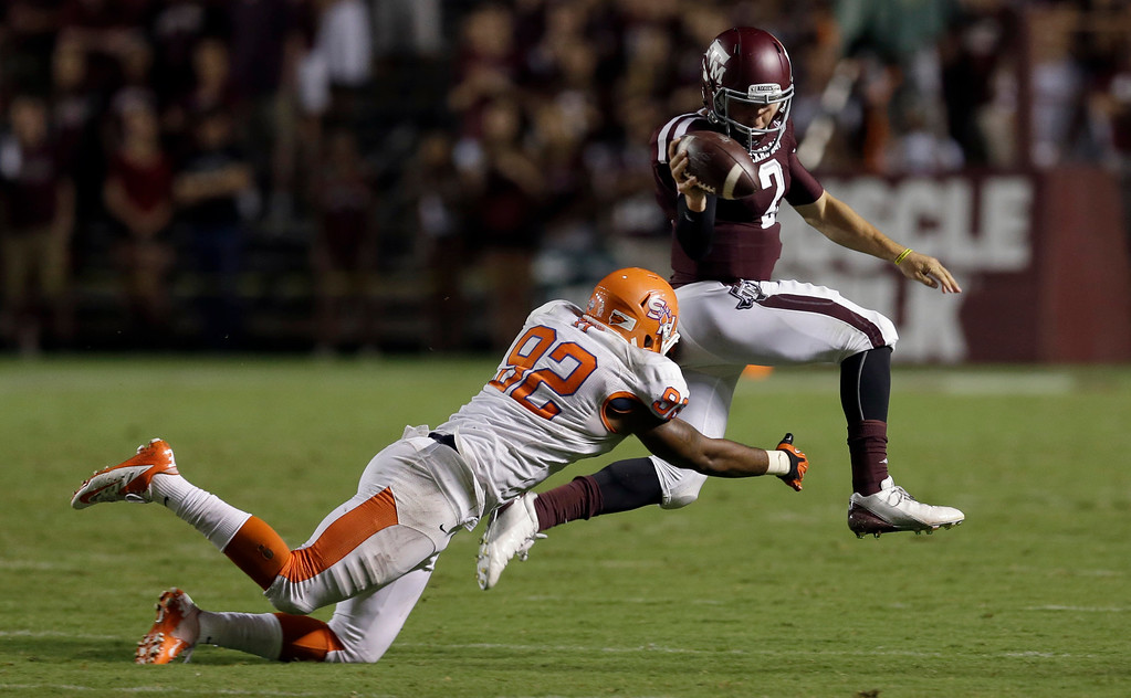 . Texas A&M quarterback Johnny Manziel (2) slips away from Sam Houston State defensive end Andrew Weaver (92) during the third quarter of an NCAA college football game on Saturday, Sept. 7, 2013, in College Station, Texas. (AP Photo/David J. Phillip)