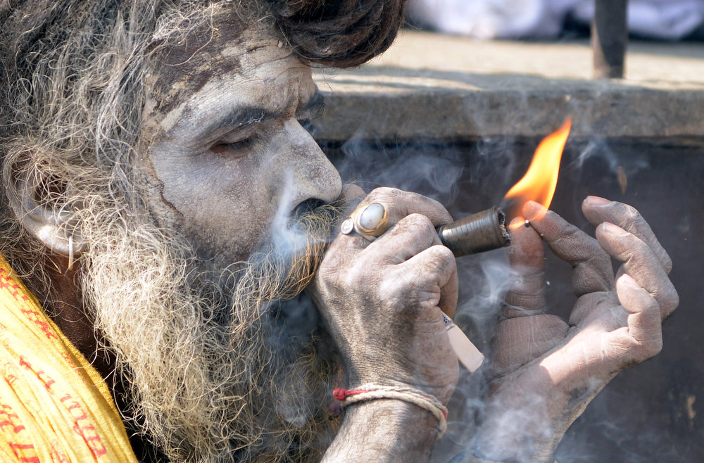 . A Sadhu smokes marijuana from a clay pipe as a holy offering for Lord Shiva, the Hindu god of creation and destruction, at the Pashupatinath temple during Maha Shivaratri in Kathmandu on March 10, 2013. Hindus mark the Maha Shivratri festival by offering special prayers and fasting. Hundreds of sadhu arrived in Pashupatinath to take part in the Maha Shivaratri festival. PRAKASH MATHEMA/AFP/Getty Images