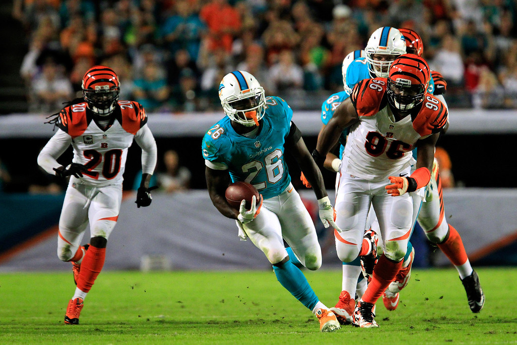 . MIAMI GARDENS, FL - OCTOBER 31: (C) Lamar Miller #26 of the Miami Dolphins runs with ball under pressure from (L) Reggie Nelson #20 of the Cincinnati Bengals and (R) Carlos Dunlap #96 of the Cincinnati Bengals at Sun Life Stadium on October 31, 2013 in Miami Gardens, Florida. (Photo by Chris Trotman/Getty Images)