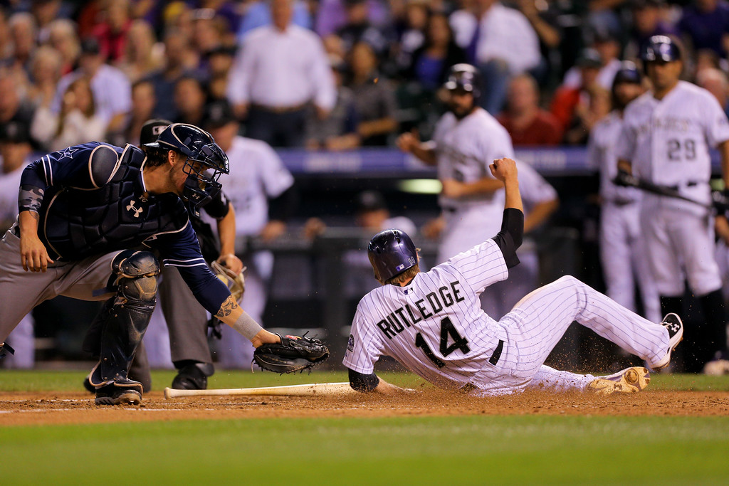 . DENVER, CO - SEPTEMBER 6:  Catcher Yasmani Grandal #8 of the San Diego Padres is late to apply the tag as Josh Rutledge #14 of the Colorado Rockies slides in to score during the fifth inning at Coors Field on September 6, 2014 in Denver, Colorado. (Photo by Justin Edmonds/Getty Images)