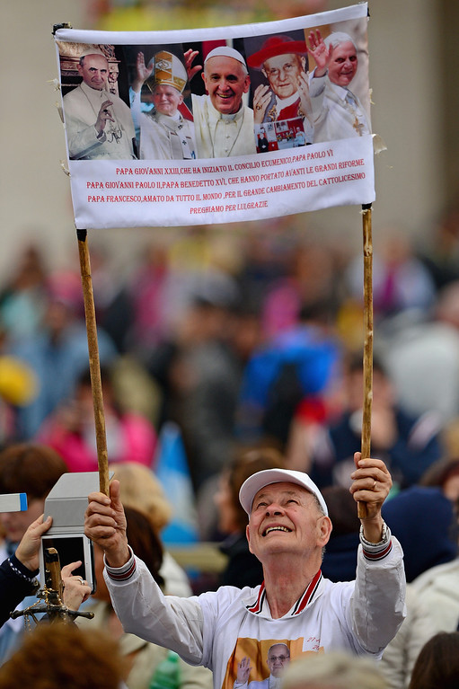 . Pilgrims gather in Saint Peter\'s Square prior to a ceremony in which John Paul II and John XXIII are to be declared saints on April 27, 2014 in Vatican City, Vatican. Dignitaries, heads of state and Royals from Europe and across the World are to attend the canonisations.  (Photo by Jeff J Mitchell/Getty Images)