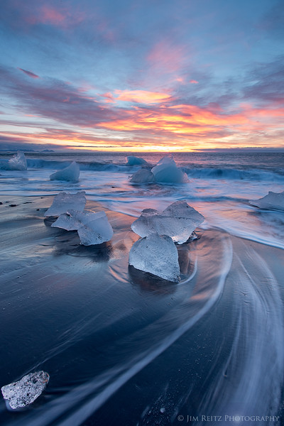 Dawn light illuminates icebergs on the black sand beach near Jökulsárlón glacier lagoon, eastern Iceland.