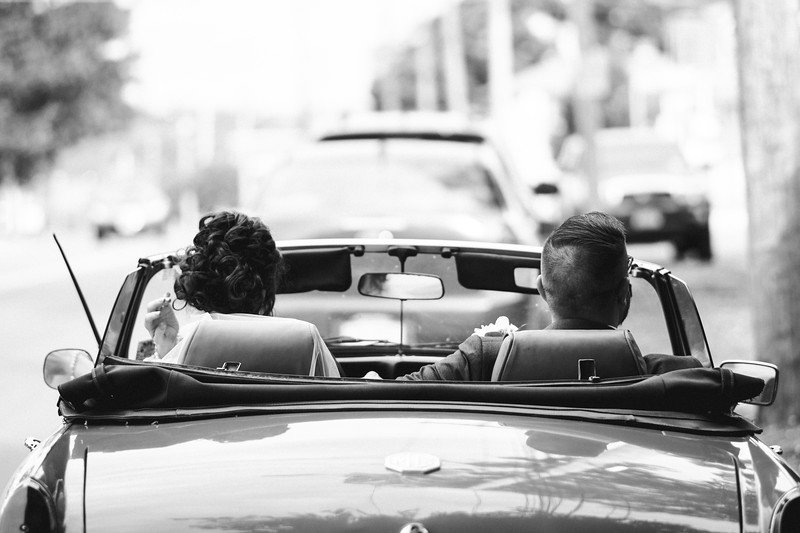 The back of the bride and grooms heads as they are about to speed away in the convertible.