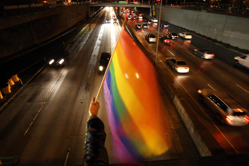 . LOS ANGELES, CA - MARCH 04:  A marcher waves a gay rainbow flag over the 101 freeway as same-sex marriage supporters rally on the eve of a state Supreme Court hearing on Proposition 8, the initiative that changed the Constitution to make gay marriage illegal, on March 4, 2009 in Los Angeles, California. An estimated 18,000 same-sex couples were married from May 16, 2008 when the state Supreme Court in a 4-3 decision ruled that the state\'s constitution gives gays and lesbians the right to marry, and November 4  when voters approved Propostion 8.  The court is scheduled to hear oral arguments and related court petitions tomorrow seeking to overturn the measure.   (Photo by David McNew/Getty Images)