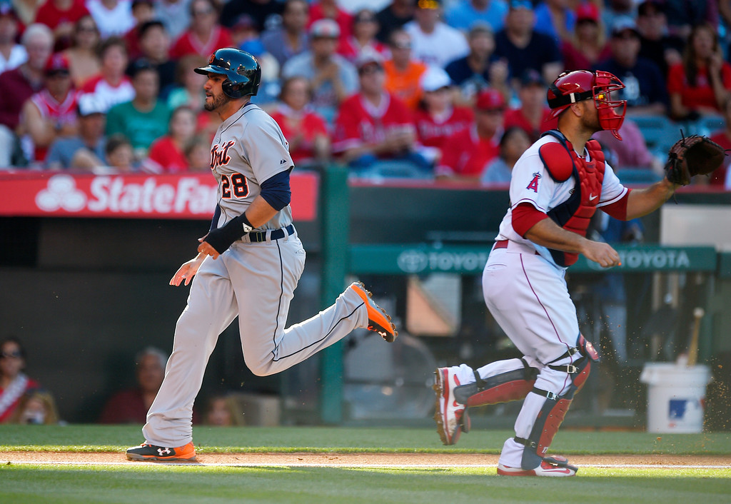 . Detroit Tigers\' J.D. Martinez, left, scores on a sacrifice fly by James McCann as Los Angeles Angels catcher Chris Iannetta takes a late throw during the second inning of a baseball game, Sunday, May 31, 2015, in Anaheim, Calif. (AP Photo/Mark J. Terrill)