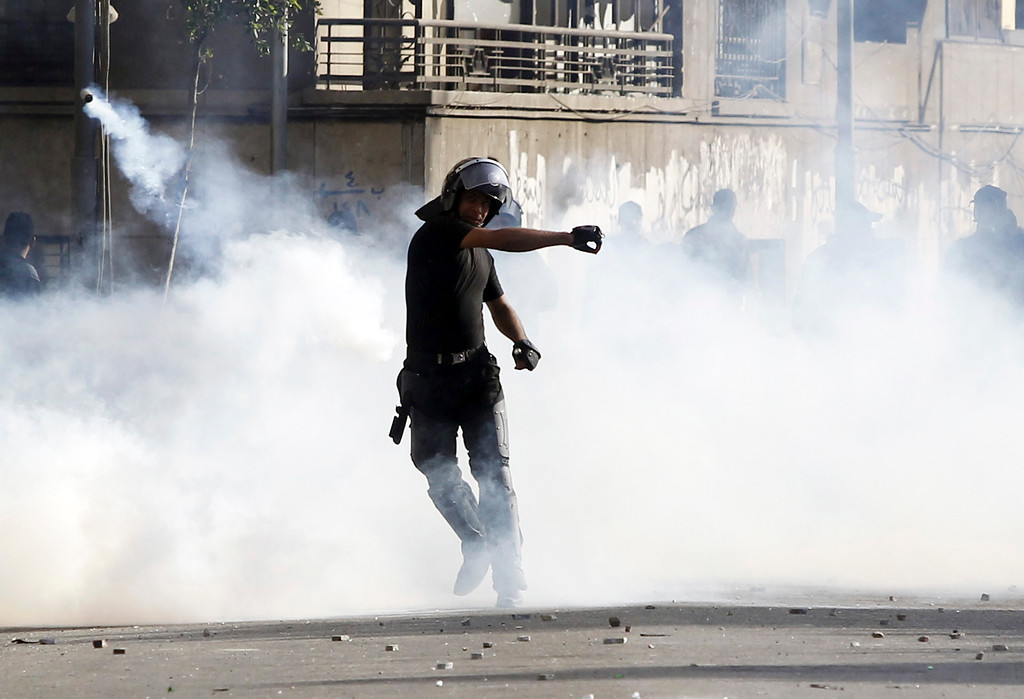 . A riot policeman throws a tear gas canister which was thrown back by protesters opposing Egyptian President Mohamed Mursi during clashes along Qasr Al Nil bridge, which leads to Tahrir Square in Cairo  March 9, 2013.  REUTERS/Amr Abdallah Dalsh