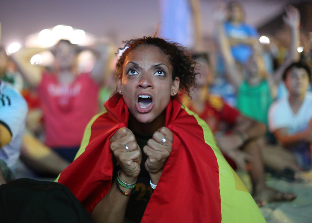 . A Spain soccer fan reacts in frustration as she watches the live broadcast of the World Cup match between Spain and the Netherlands inside the FIFA Fan Fest area on Copacabana beach in Rio de Janeiro, Brazil, Friday, June 13, 2014. The Netherlands thrashed Spain 5-1 Friday. It was a humiliating defeat for the defending World Cup champions. (AP Photo/Leo Correa)
