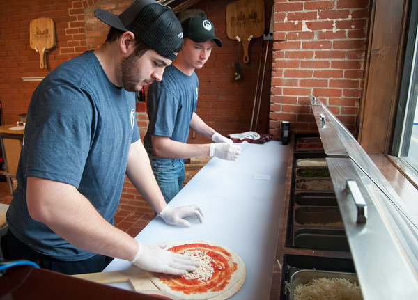 03/30/18 Wesley Bunnell | Staff 5 Churches Brewing held their ribbon cutting with city officials on Friday at noon to a crowd of customers lined down the sidewalk. Jacob Larche prepares a pizza as James Cox, rear, waits to place it in the brick oven.