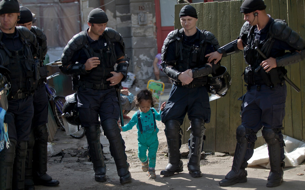 . A Roma child walks between riot policemen during the eviction of more than 100 people from the homes they lived in Bucharest, Romania, Monday, Sept. 15, 2014. (AP Photo/Vadim Ghirda)