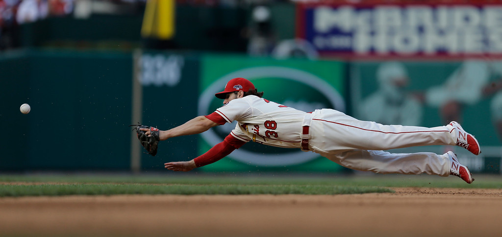 . St. Louis Cardinals\' Pete Kozma can\'t catch a wild throw from teammate Matt Carpenter during the sixth inning of Game 2 of the National League baseball championship series against the Los Angeles Dodgers Saturday, Oct. 12, 2013, in St. Louis. (AP Photo/Jeff Roberson)