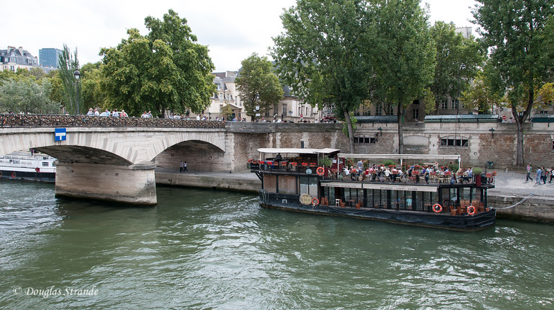 One of many bridges over the River Seine and a touring riverboat