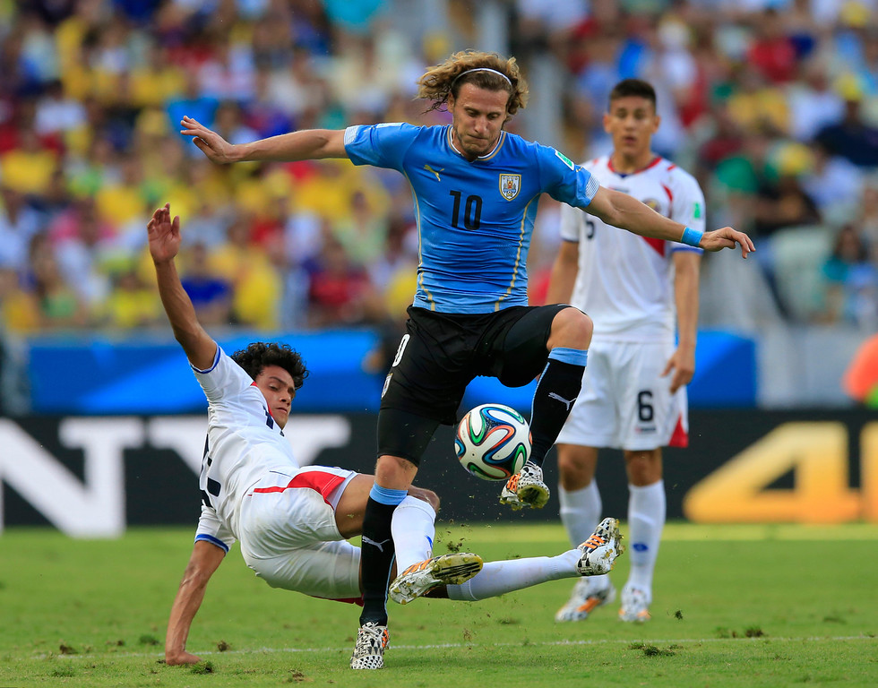 . Uruguay\'s Diego Forlan, right, is challenged by Costa Rica\'s Yeltsin Tejeda during the group D World Cup soccer match between Uruguay and Costa Rica at the Arena Castelao in Fortaleza, Brazil, Saturday, June 14, 2014. (AP Photo/Bernat Armangue)