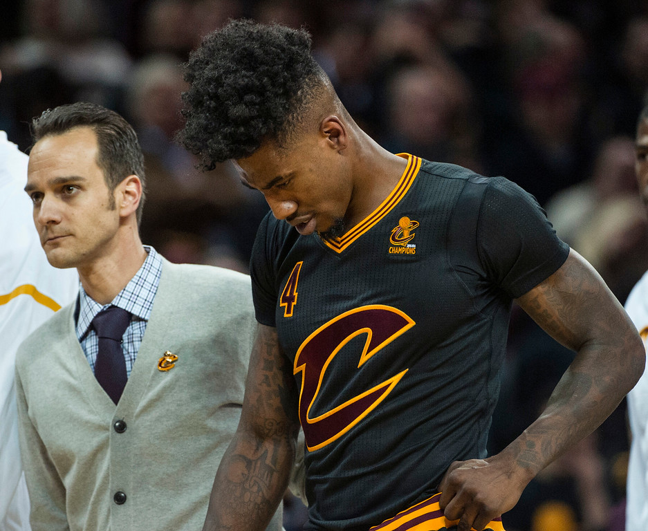 . Cleveland Cavaliers\' Iman Shumpert walks off the court with an unidentified medical aid after being injured during the second half of an NBA basketball game against the New York Knicks in Cleveland, Tuesday, Oct. 25, 2016. The Cavaliers won 117-88. (AP Photo/Phil Long)