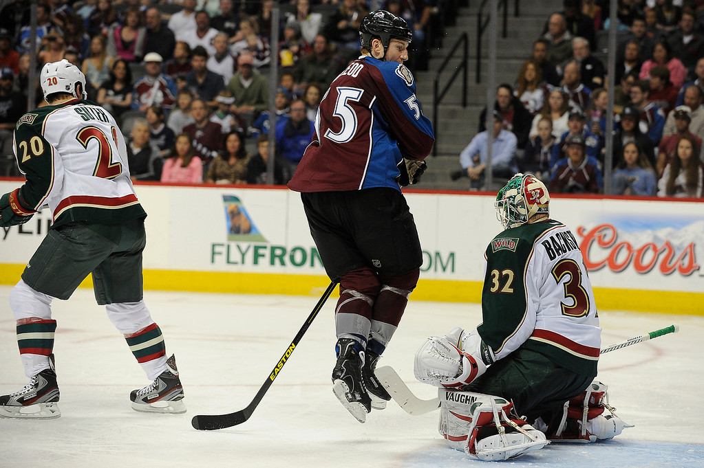. Cody McLeod (55) of the Colorado Avalanche leaps in the air as he tries to get out of the way of the puck while screening Minnesota Wild goalie (32) Niklas Backstrom during the third period, Saturday, April 27, 2012 at Pepsi Center. Seth A. McConnell, The Denver Post