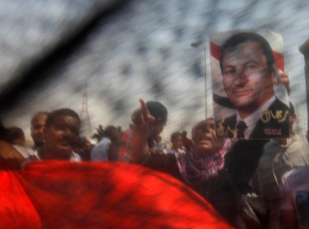 ". Supporters of Egypt\'s former Egyptian President Hosni Mubarak hold a poster of him and chant slogans in front of Torah Prison where he has been held, in Cairo, Egypt, Thursday, Aug. 22, 2013. The Arabic writing on the poster reads ""men of Mubarak.\"" Egypt\'s ousted leader Hosni Mubarak, wearing a white shirt and loafers while flashing a smile, was released from prison Thursday and transported to a military hospital in a Cairo suburb where he will be held under house arrest. (AP Photo/Amr Nabil)"