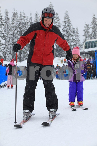 Father teaches his five-year old daughter how to ski.