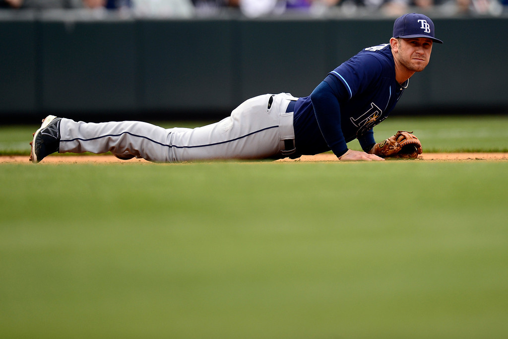 . DENVER, CO - MAY 5: Evan Longoria (3) of the Tampa Bay Rays lays on the ground after Nolan Arenado (28) of the Colorado Rockies poked a hit through the hole during the Rockies\' 8-3 loss.   (Photo by AAron Ontiveroz/The Denver Post)